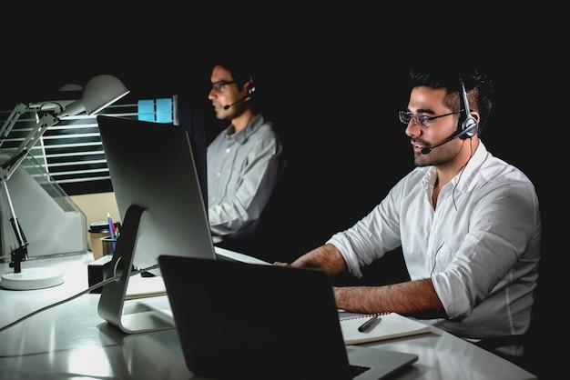 Aasian equipe de suporte técnico trabalhando turno da noite em call center