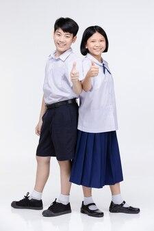 Aasian menina e menino em uniforme de estudante em cinza