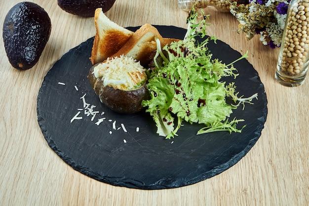 Abacate assado com ovo, queijo e croutons em uma placa de ardósia preta ... comida saudável, mesa de madeira