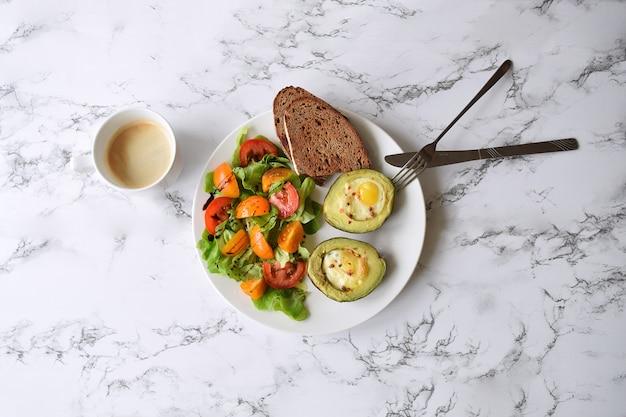 Abacate assado com ovos de codorna salat de tomate e pão xícara de capuccino