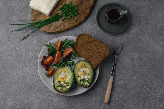 Abacate assado, rúcula, tomate cereja, pão integral ao lado de queijo feta, cebolinha na tábua de madeira, café expresso