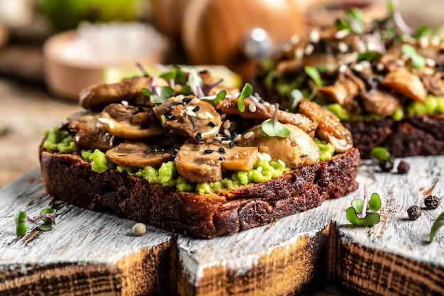 Abacate, cogumelos e sanduíche microgreen de grãos inteiros