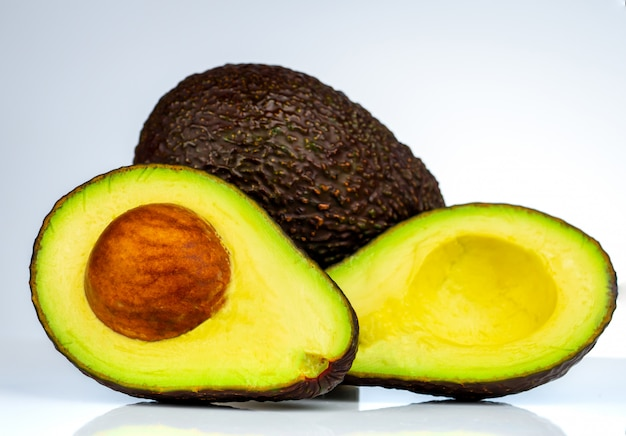 Abacate com a semente isolada no fundo branco. fonte de ômega 3 de alimentos naturais. comida saudável para o bebê. metade de pedaços de abacates arranjados com belo padrão. alimentos orgânicos para vegetarianos.