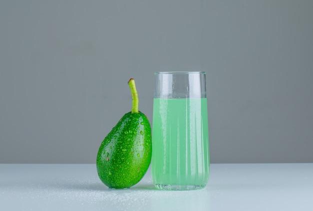Abacate com bebida na mesa branca e cinza, vista lateral.