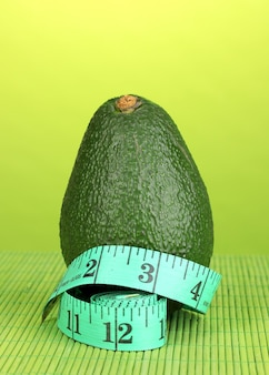 Abacate com fita métrica na superfície verde
