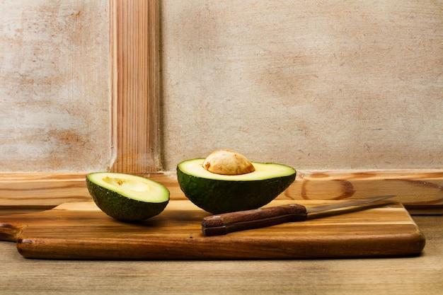 Abacate cortado ao meio em uma placa de cozinha de madeira