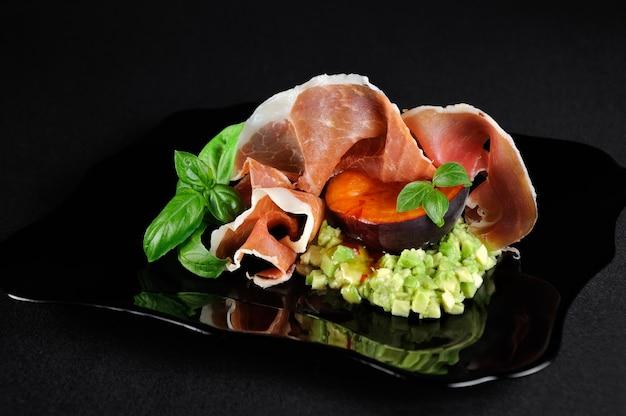Abacate de carne com uma fatia de damasco preto com molho picante quente e doce e presunto de parma