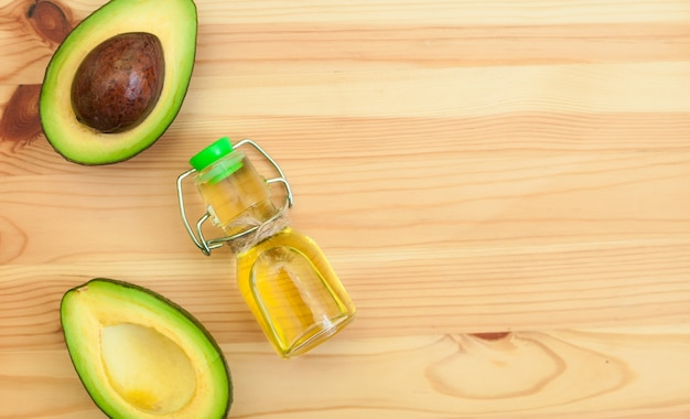 Abacate e óleo de abacate na garrafa no fundo de madeira.