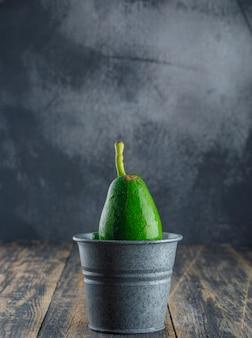 Abacate em um mini balde na parede de madeira e gesso. vista lateral.
