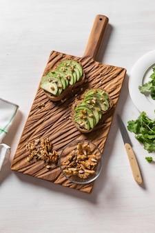 Abacate fatiado em pão torrado com café da manhã nozes e conceito de comida saudável vista superior