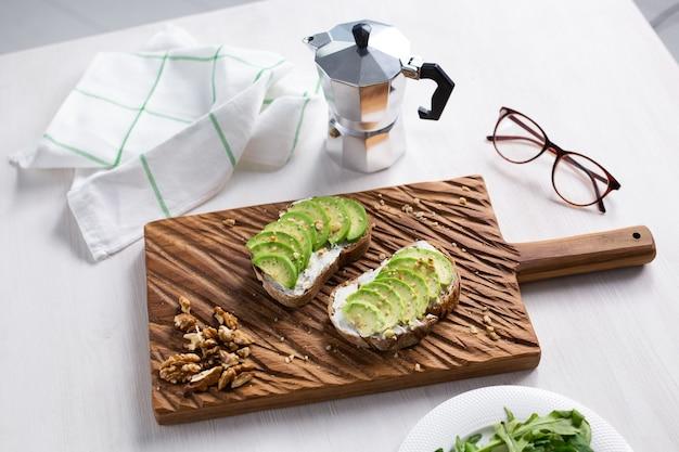 Abacate fatiado em pão torrado com café da manhã nozes e conceito de comida saudável