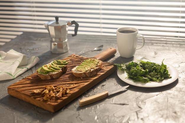 Abacate fatiado em pão torrado com nozes e espinafre de café em um prato e café da manhã pote moka e
