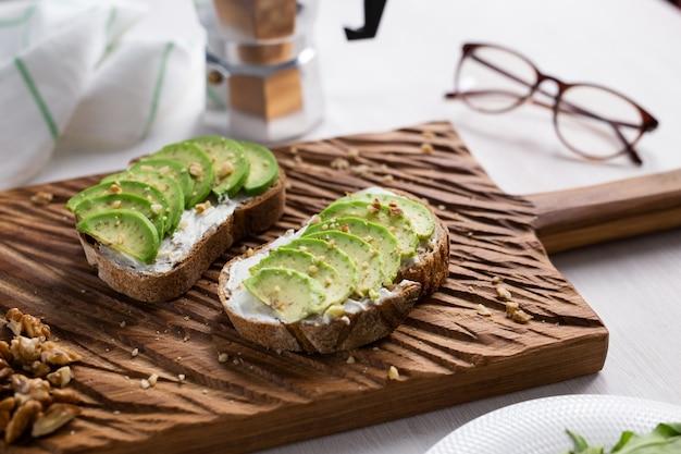 Abacate fatiado na torrada de pão com nozes. café da manhã e o conceito de comida saudável.