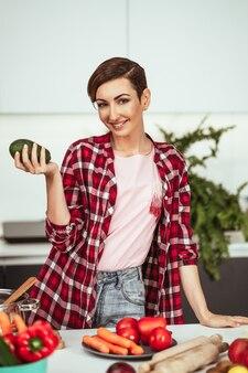 Abacate fresco nas mãos de uma linda dona de casa com um penteado curto prepara a comida na cozinha