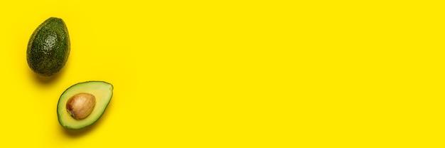 Abacate inteiro e meio em um fundo amarelo brilhante. vista superior, configuração plana. bandeira.