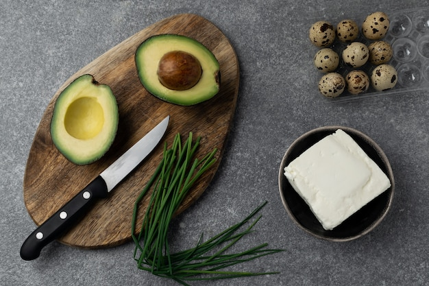 Abacate na tábua de madeira, ovos de codorna, queijo feta, cebolinha, mesa cinza