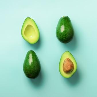 Abacate orgânico com semente, metades do abacate e frutos inteiros no fundo azul. teste padrão verde dos abacates no estilo mínimo da configuração do plano.