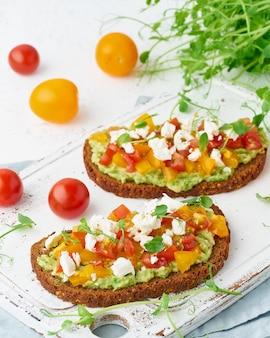 Abacate torrada com queijo feta e tomate, smorrebrod com ricota, closeup e vertical