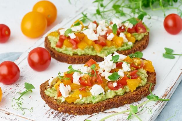 Abacate torrada com queijo feta e tomate, smorrebrod com ricota, closeup