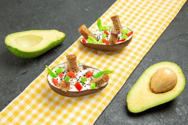 Abacates cremosos de frente com pão e pimenta no espaço cinza