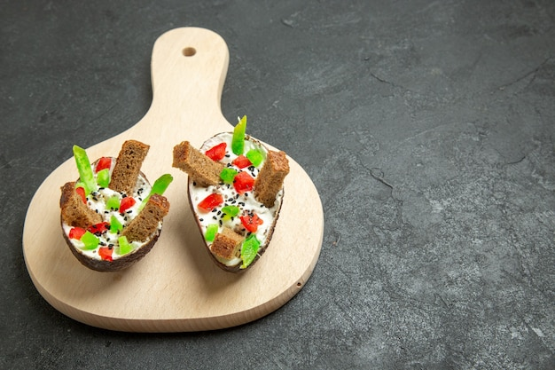 Abacates cremosos de frente com pimentas fatiadas e pedaços de pão no espaço cinza