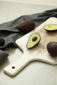 Abacates inteiros e cortados em tábua de madeira