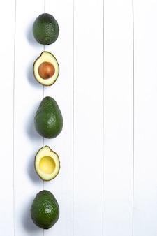 Abacates isolados em um fundo branco de madeira. vista do topo. formato vertical com copyspace.
