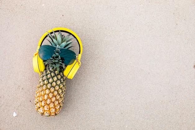 Abacaxi atraente maduro em elegantes óculos de sol espelhados e fones de ouvido dourados na areia contra a água do mar turquesa. conceito de férias de verão tropical.