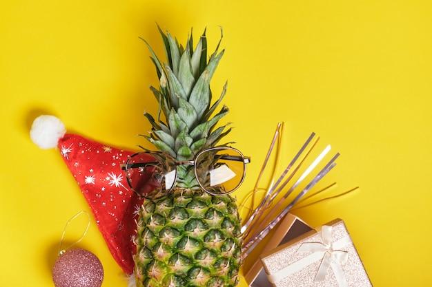 Abacaxi, chapéu de papai noel e óculos de sol, decoração de natal em fundo amarelo