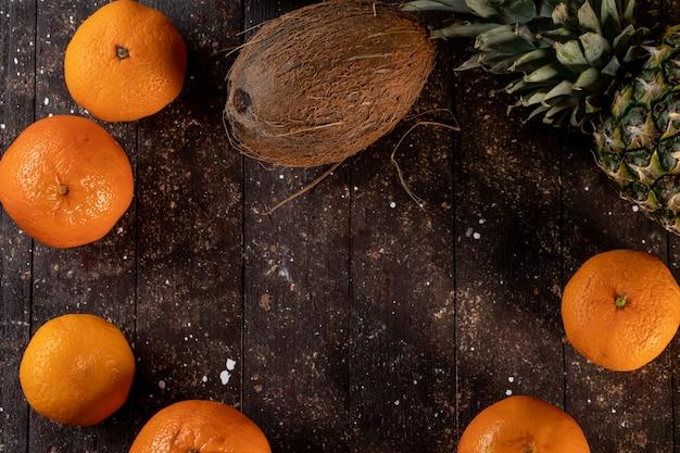 Abacaxi coco e tangerina em uma mesa de madeira