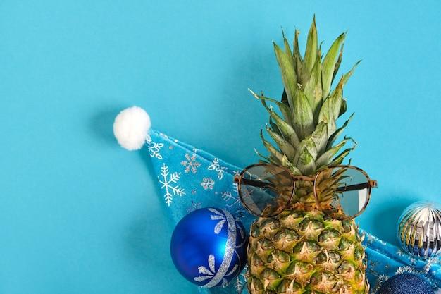 Abacaxi com chapéu de papai noel e óculos de sol, decoração de natal em fundo azul, conceito de férias de inverno nos trópicos