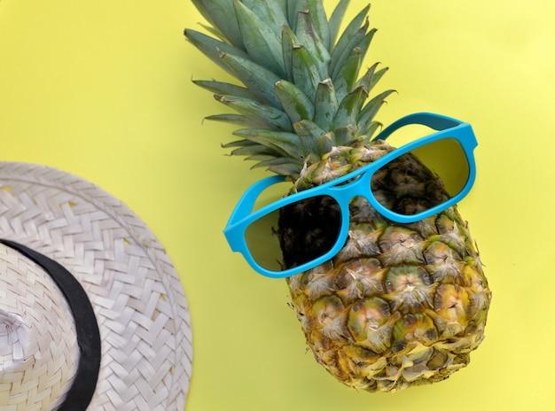 Abacaxi com óculos de sol azuis e chapéu de palha no fundo amarelo