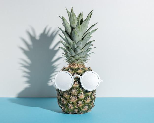 Abacaxi com óculos de sol brancos sobre fundo azul.