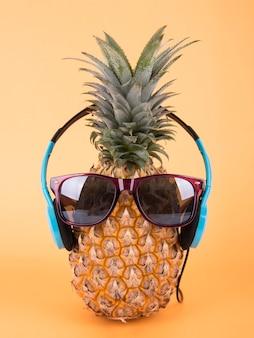 Abacaxi com óculos de sol e auscultadores no fundo alaranjado. conceito de fruta verão.