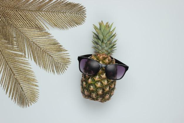 Abacaxi com óculos de sol e folhas de palmeira douradas sobre fundo branco. conceito tropical. vista do topo