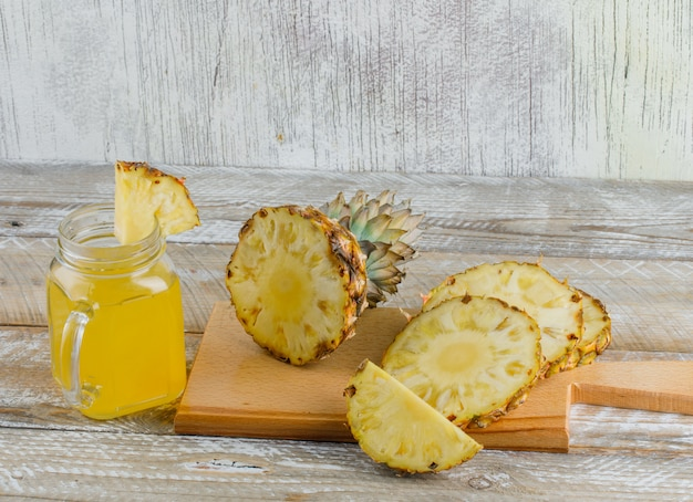 Abacaxi com suco e tábua na superfície de madeira e suja