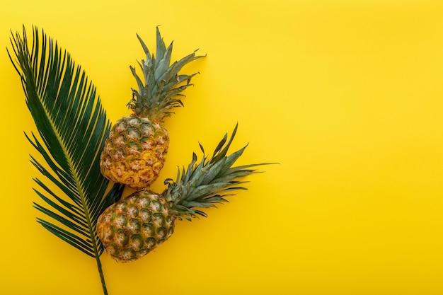 Abacaxi e folhas de palmeira em fundo de cor amarela do verão. abacaxi verão tropical frutas plana composição leiga com espaço de cópia. banco de fotos de alta qualidade