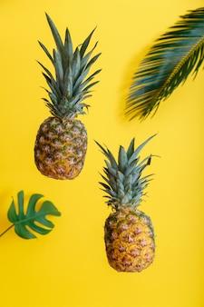 Abacaxi e folhas de palmeira em fundo de cor amarela do verão. frutas tropicais do verão levitando abacaxis.
