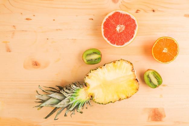 Abacaxi e frutas cítricas na mesa de madeira