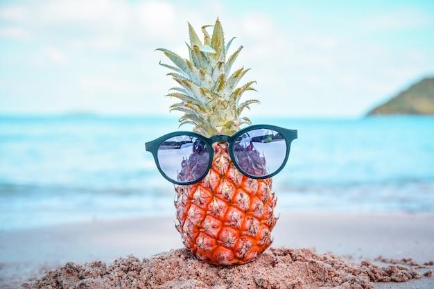 Abacaxi e óculos de sol na praia st mar verão
