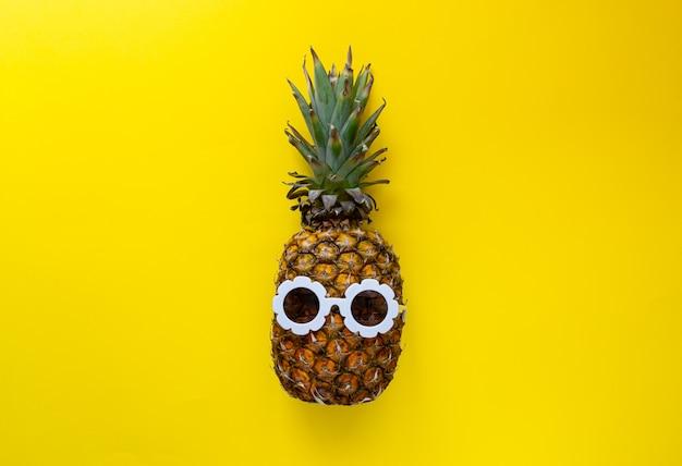 Abacaxi em óculos de sol brancos sobre o fundo colorido, conceito criativo de verão