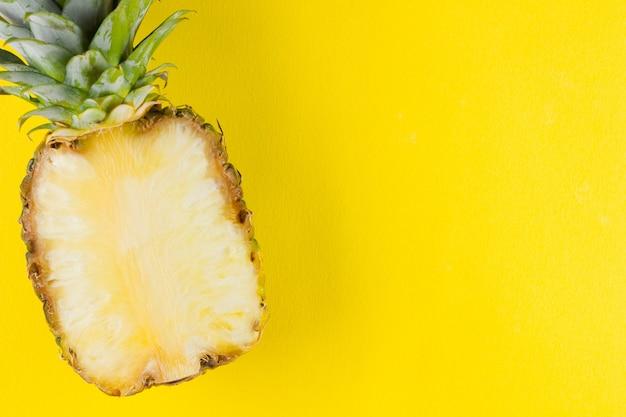 Abacaxi em um fundo amarelo. metade do abacaxi em um fundo pastel. frutas tropicais em estilo pop art. minimalismo. copyspace