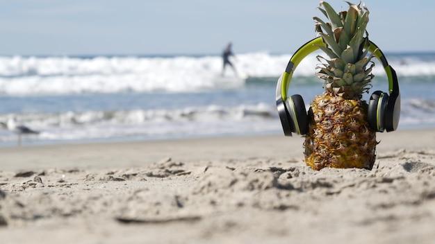 Abacaxi engraçado em fones de ouvido, praia de areia do oceano, ondas de água do mar azul, costa do pacífico da califórnia, eua. frutas exóticas de verão tropical curtindo férias e música no paraíso. ananas tomando sol na praia