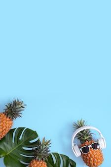 Abacaxi engraçado usando fone de ouvido branco, conceito de ouvir música, isolado em um fundo azul com folhas de palmeira tropical, vista superior, design plano leigo