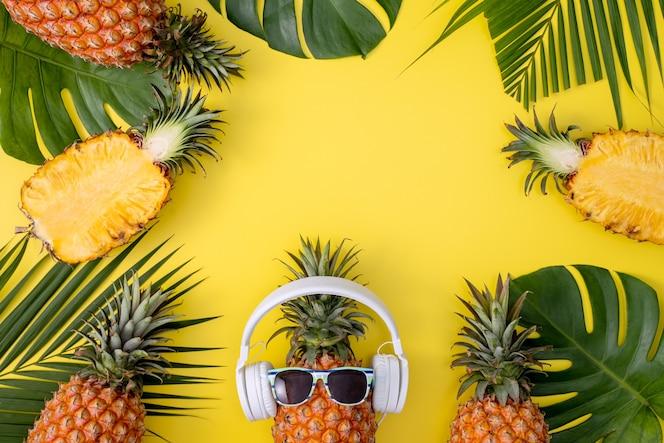 Abacaxi engraçado usando fone de ouvido branco, ouvir música, isolado em um fundo amarelo com folhas de palmeira tropical, vista superior, conceito de design plano leigo.