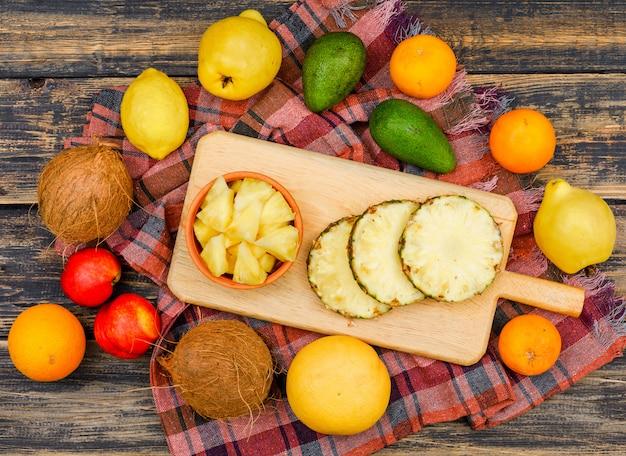 Abacaxi fatiado em uma tábuas de madeira e tigela com coco, pêssegos, marmelos e frutas cítricas vista superior em uma superfície de madeira grunge e pano de piquenique