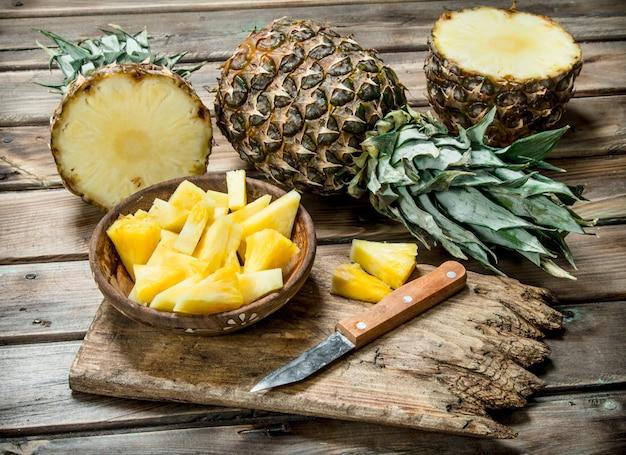 Abacaxi fatiado em uma tigela em uma placa de corte com uma faca e um abacaxi inteiro. em fundo de madeira