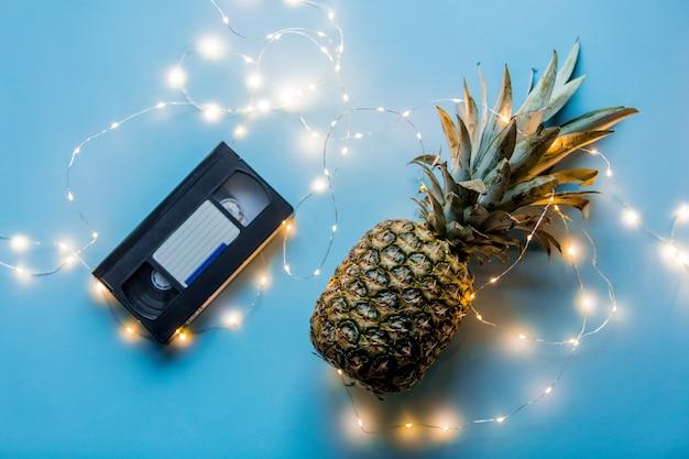 Abacaxi fresco com luzes de fada e cassete vhs sobre fundo azul.