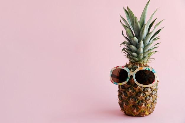 Abacaxi fresco em óculos de sol. conceito de descanso, viagens, férias, relaxamento.