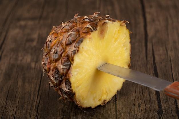 Abacaxi fresco tropical com faca na superfície de madeira.